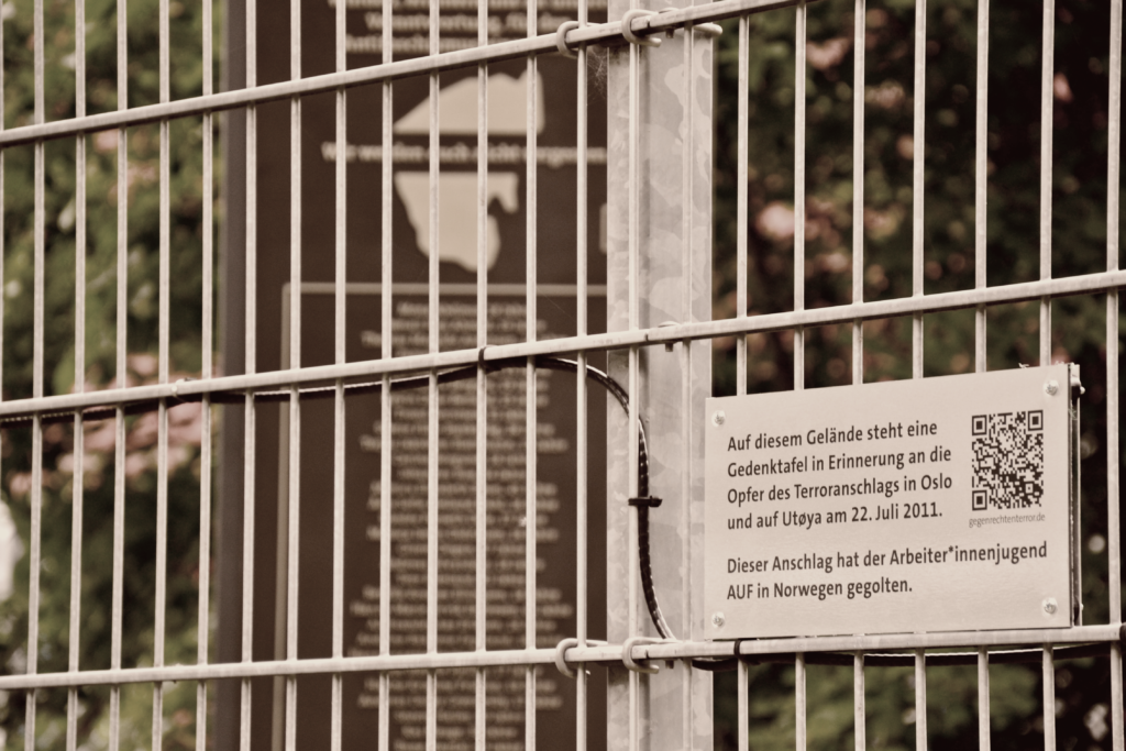 Im Vordergrund des Bildes sieht man eine Tafel die am Zaun des Anton-Schmaus-Hauses angebracht ist und die auf das Denkmal im Hintergrund und aud das Bildungsmaterial zum Denkmal verweist.