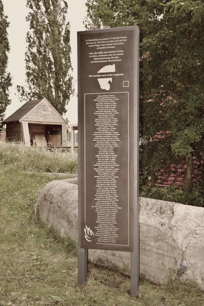 Das Denkmal für die Ermordeten am 22. Juli 2011 in Oslo und Utøya steht in der Mitte des Bildes und im Hintergrund sieht man ein Gebäude mit einem Falken-Logo drauf.
